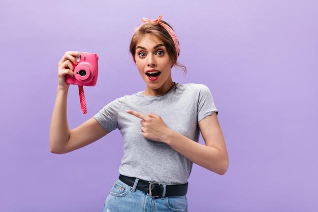 Zdziwiona kobieta w szarej koszuli trzyma różowy aparat. urocza młoda dziewczyna w stylową fryzurę z opaską pozowanie. n na białym tle.