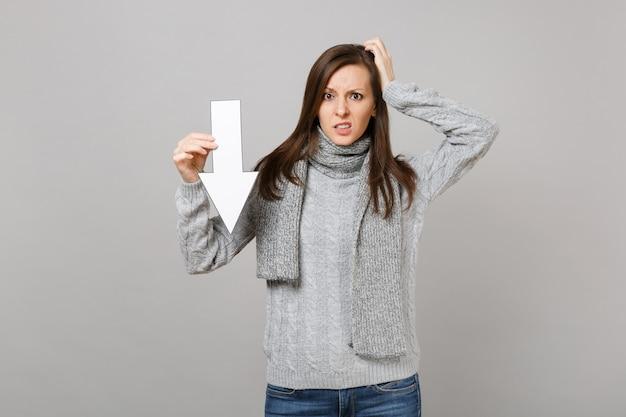 Zdziwiona kobieta w szarym swetrze, szalik położył rękę na głowie przytrzymaj strzałkę spadku wartości na białym tle na szarym tle. zdrowa moda styl życia ludzie szczere emocje koncepcja zimnej pory roku. makieta miejsca na kopię.