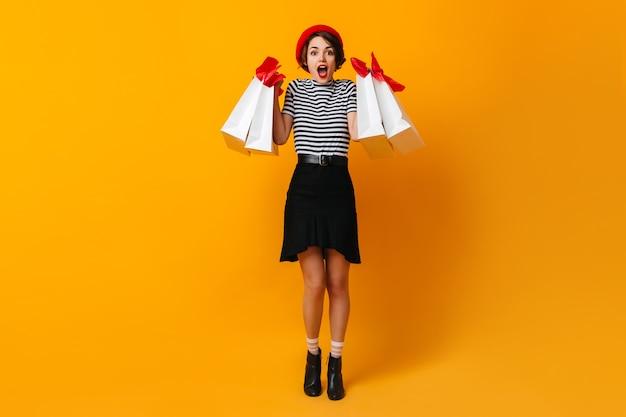Zdziwiona kobieta w t-shirt w paski pozuje po zakupach