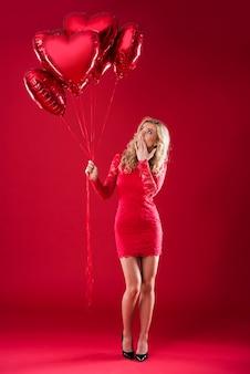 Zdziwiona kobieta z bukietem balonów