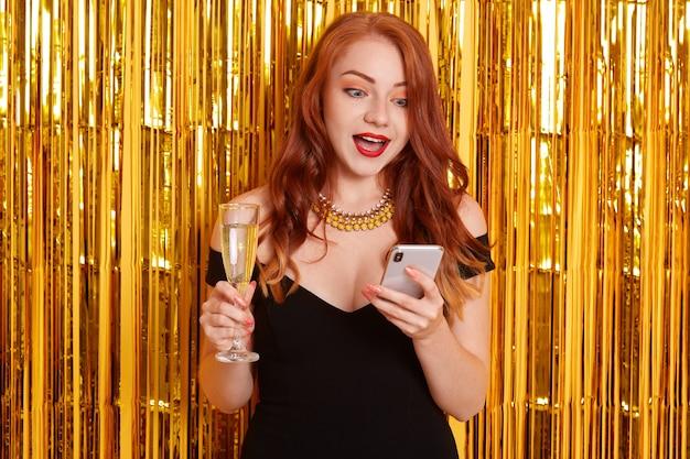 Zdziwiona kobieta z czerwonymi ustami i szeroko otwartymi ustami, patrząc zszokowanym wyrazem twarzy na swoje urządzenie, dziewczyna ubrana w czarną sukienkę, pozująca odizolowana na ścianie ozdobionej złotym świecidełkiem.