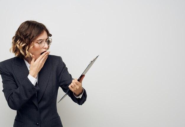 Zdziwiona kobieta z dokumentami w rękach makieta biura pracy