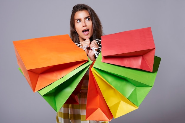 Zdziwiona kobieta z dużą ilością toreb na zakupy
