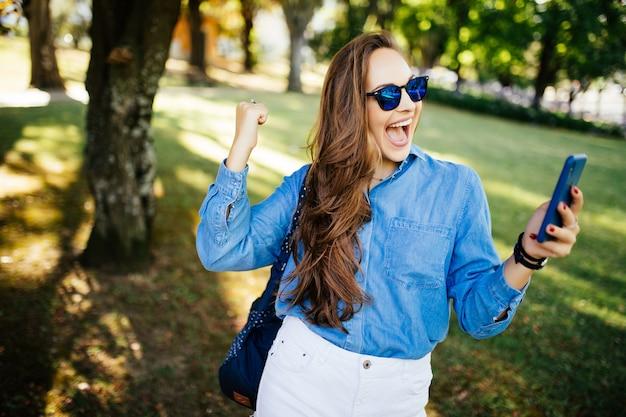 Zdziwiona kobieta, z krzykiem zwycięstwa patrzy na telefon i dostaje dobre wieści na świeżym powietrzu w parku
