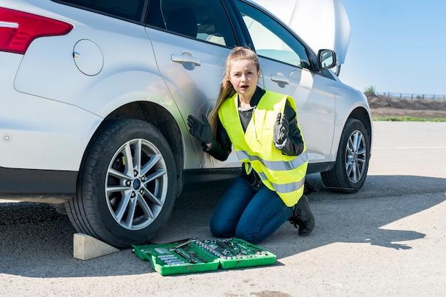 Zdziwiona kobieta z narzędziami i zepsutym samochodem na poboczu drogi