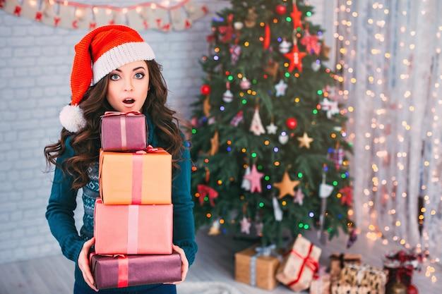 Zdziwiona kobieta z prezentami i choinką. wyprzedaż świąteczna.