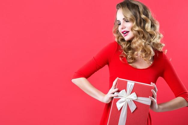Zdziwiona kobieta z pudełkiem w czerwonej sukience. piękna dziewczyna z kręconymi włosami.