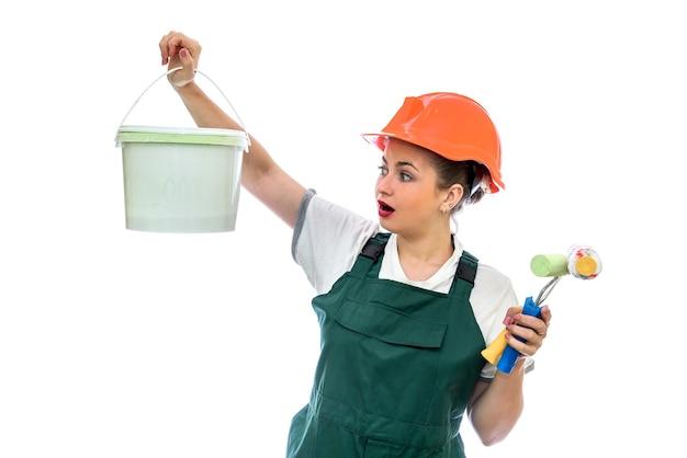 Zdziwiona kobieta z wiadrem z farbą i narzędziami do malowania