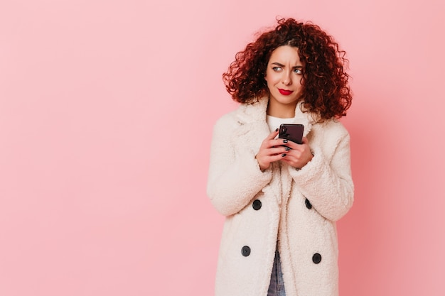 Zdziwiona kręcona brunetka dziewczyna w białym zimowym stroju trzyma czarnego smartfona na różowej przestrzeni.