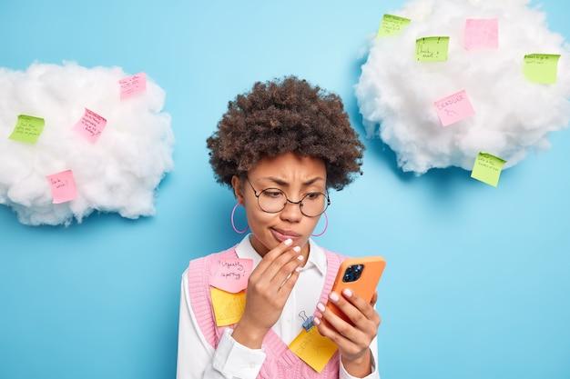 Zdziwiona, kręcona, zapracowana kobieta w biurze ma wiele planów na dzień powszedni skoncentrowany na czytaniu wiadomości na smartfonie otoczonym kolorowymi karteczkami, aby nie zapomnieć o pilnych rzeczach do zrobienia