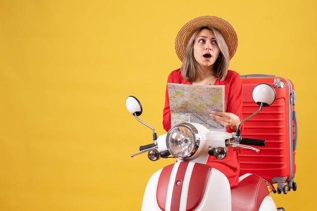 Zdziwiona ładna dziewczyna na motorowerze z czerwoną walizką trzymającą mapę