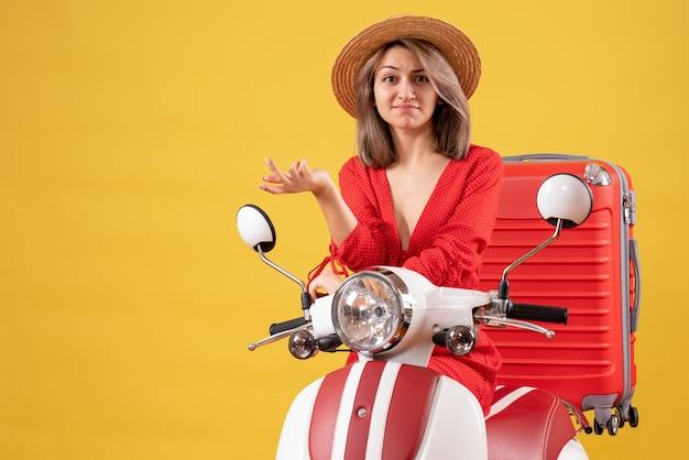 Zdziwiona ładna dziewczyna na motorowerze z walizką