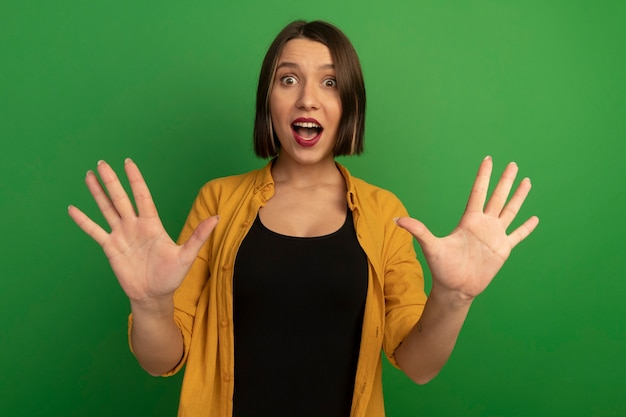 Zdziwiona ładna kobieta stoi z uniesionymi rękami na białym tle na zielonej ścianie