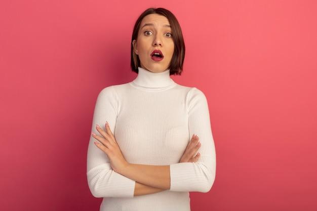 Zdziwiona ładna kobieta stoi ze skrzyżowanymi rękami na białym tle na różowej ścianie