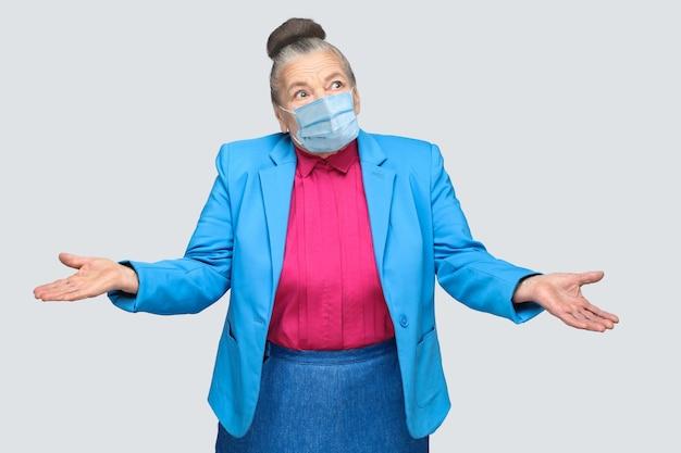 Zdziwiona lub zdezorientowana stara kobieta z chirurgiczną maską medyczną, uniesionymi rękami. babcia w jasnoniebieskim garniturze i różowej koszuli stojąca z zebranym kokiem siwych włosów. strzał w pomieszczeniu, na białym tle na szarym tle