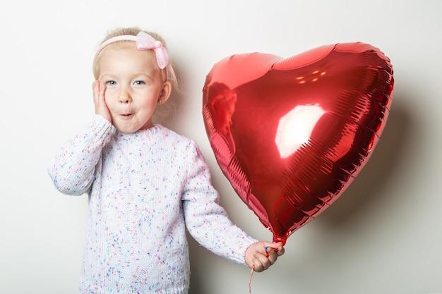 Zdziwiona mała dziewczynka trzyma balon serce na jasnym tle. koncepcja na walentynki, urodziny. transparent.