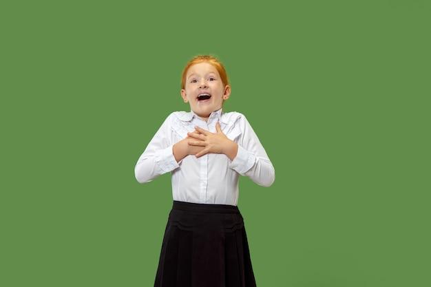 Zdziwiona mała szczęśliwa dziewczyna na białym tle na zielonej ścianie