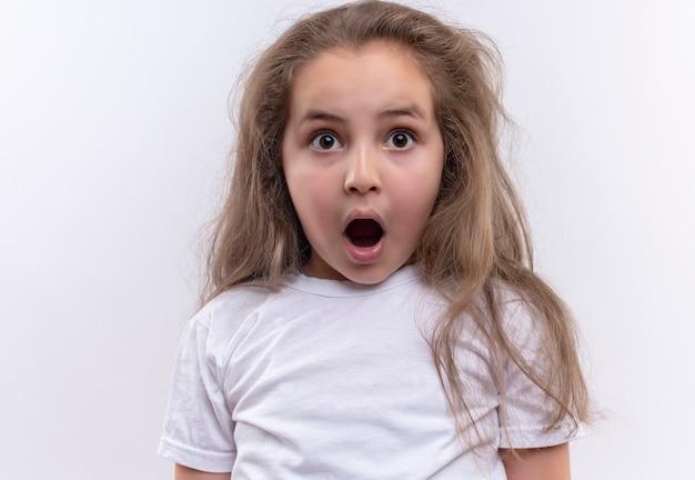 Zdziwiona mała uczennica ubrana w białą koszulkę otworzyła usta na na białym tle