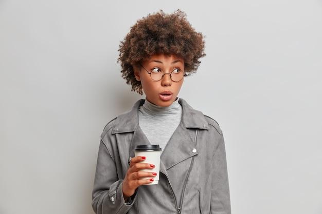Zdziwiona młoda afro kobieta, ubrana w szarą marynarkę, pije kawę na wynos