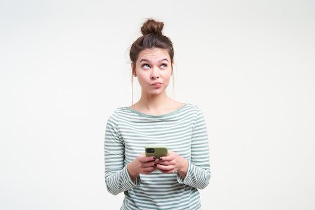 Zdziwiona młoda atrakcyjna brązowowłosa dama wydymająca usta, patrząc w zadumie w górę, trzymając telefon komórkowy w uniesionych dłoniach, pozując na białej ścianie