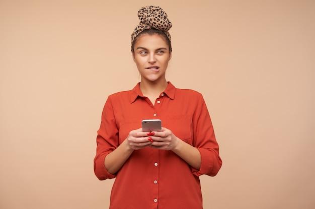 Zdziwiona młoda atrakcyjna brązowowłosa dama z telefonem komórkowym w dłoniach mrużąc oczy i gryząc w zamyśleniu pod wargą, pozując na beżowej ścianie