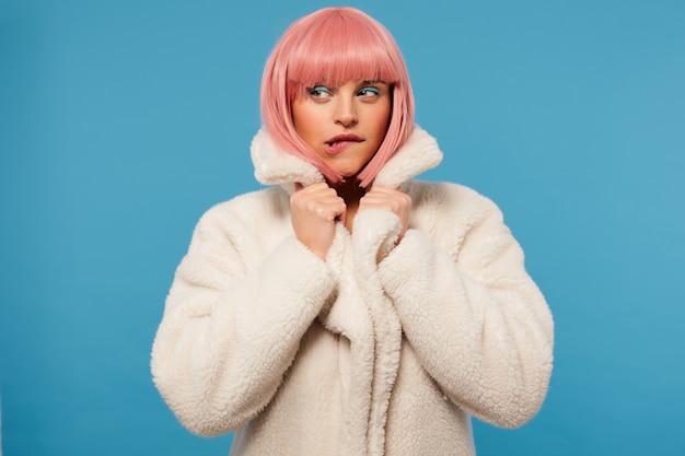 Zdziwiona młoda atrakcyjna różowowłosa kobieta z świątecznym makijażem, ubrana w białe fantazyjne ubrania, gryząca dolną wargę i spoglądająca zamyślona na bok