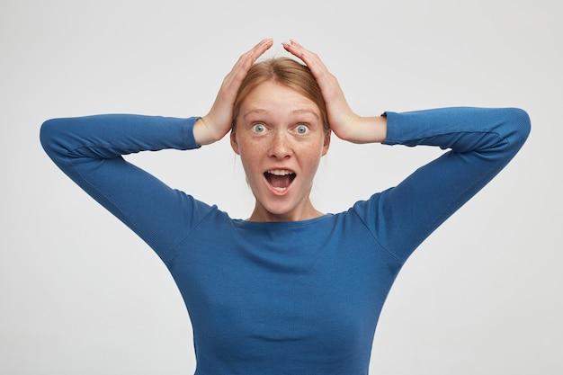 Zdziwiona młoda atrakcyjna ruda kobieta patrzy z podekscytowaniem na aparat z szeroko otwartymi oczami i ustami, ściskając głowę z uniesionymi rękami podczas pozowania na białym tle