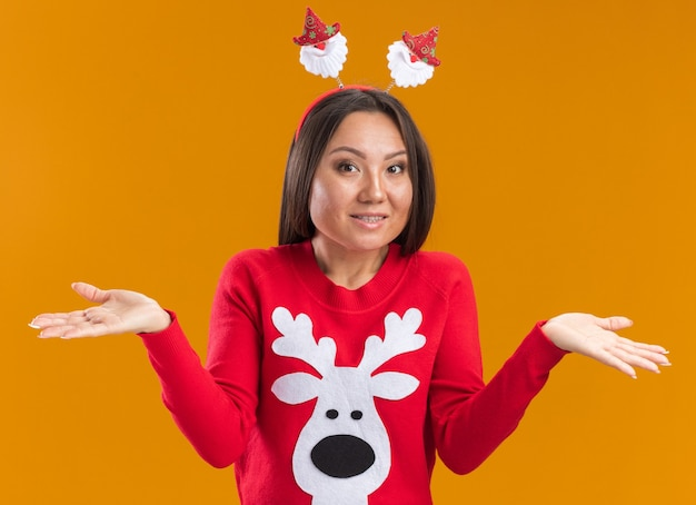 Zdziwiona młoda azjatycka dziewczyna ubrana w boże narodzenie obręcz do włosów ze swetrem, rozkładając ręce na białym tle na pomarańczowej ścianie