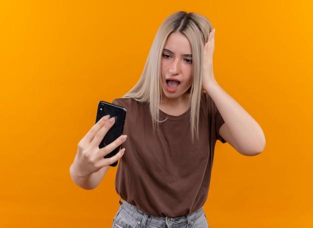 Zdziwiona młoda blondynka trzyma telefon komórkowy, patrząc na to ręką na głowie na odizolowanej pomarańczowej ścianie z miejsca na kopię