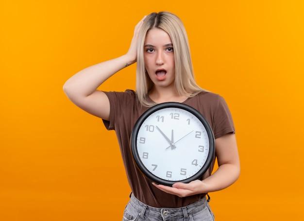 Zdziwiona młoda blondynka trzyma zegar z ręką na głowie na odosobnionej pomarańczowej ścianie z miejsca na kopię