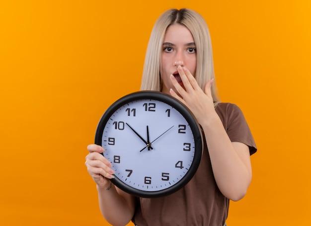 Zdziwiona młoda blondynka trzyma zegar z ręką na ustach na odosobnionej pomarańczowej ścianie z miejsca na kopię