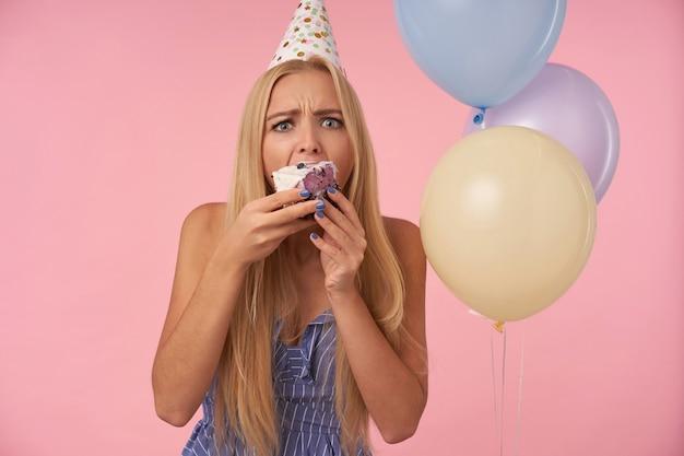 Zdziwiona młoda blondynka w świątecznych ubraniach i stożkowym kapeluszu marszcząca brwi i zaokrąglone oczy podczas jedzenia pysznego ciasta w kolorowych balonach z helem, odizolowanych na różowym tle