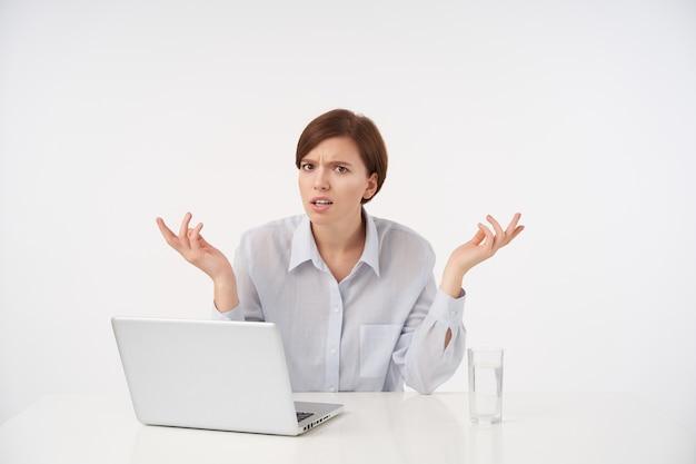 Zdziwiona młoda brązowooka krótkowłosa kobieta z naturalnym makijażem z niezadowoloną twarzą i unosząca zmieszane dłonie, siedząc na białym