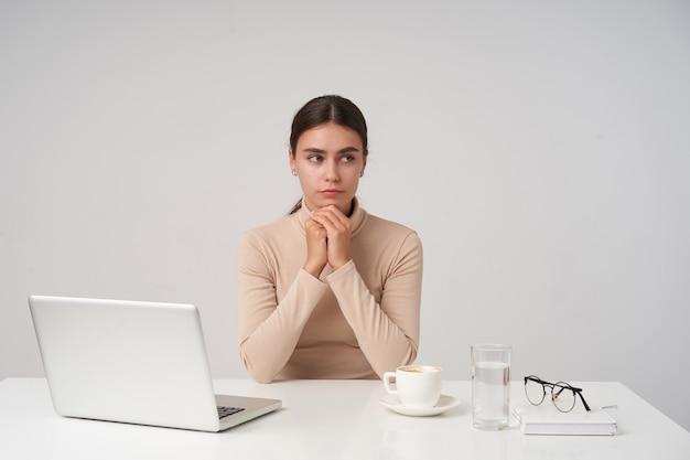 Zdziwiona młoda brunetka atrakcyjna biznesowa dama składająca ręce pod brodą, patrząc w zamyśleniu na bok, ubrana w formalne ubrania, pozując na białej ścianie