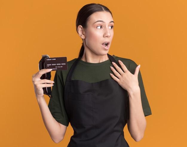 Zdziwiona młoda brunetka fryzjer dziewczyna w mundurze trzyma maszynkę do strzyżenia włosów i kartę kredytową kładzie rękę na piersi, patrząc na bok na pomarańczowo