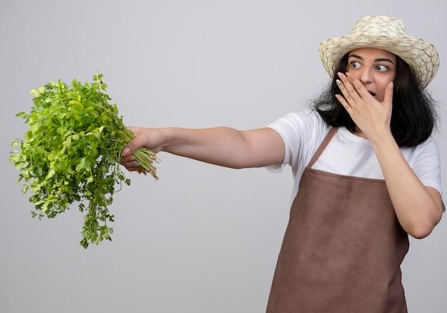 Zdziwiona młoda brunetka ogrodniczka w mundurze w kapeluszu ogrodniczym kładzie rękę na ustach i trzyma kolendrę na białej ścianie