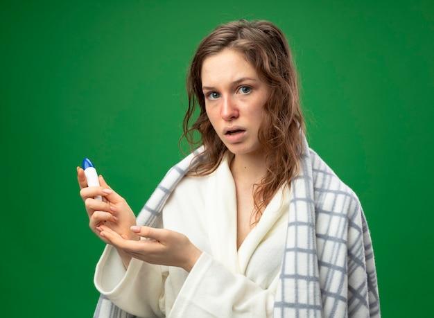 Zdziwiona młoda chora dziewczyna ubrana w białą szatę owiniętą w kratę trzymając i wskazuje ręką na termometr na białym tle na zielono