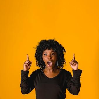 Zdziwiona młoda czarna kobieta wskazuje up w studiu