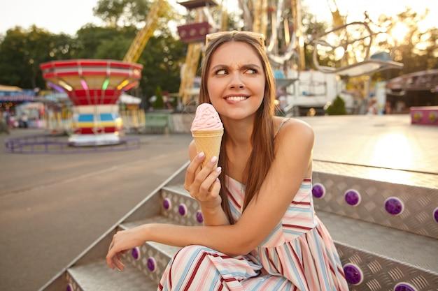 Zdziwiona młoda długowłosa kobieta z okularami przeciwsłonecznymi na głowie, patrząca na bok i marszcząca brwi, trzymająca w ręku lody w rożku, siedząca nad dekoracjami parku rozrywki