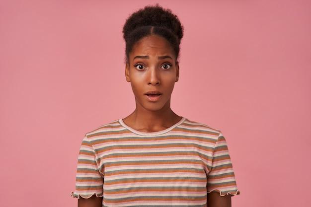 Zdziwiona młoda, dość kręcona brunettened kobieta z przypadkową fryzurą, patrząc przestraszony z przodu, stojąc nad różową ścianą w beżowej koszulce w paski