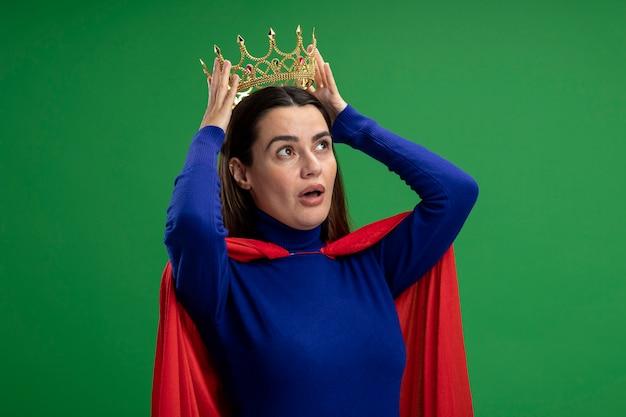 Zdziwiona młoda dziewczyna superbohatera patrząc z boku w koronie, zakładając koronę na głowę na białym tle na zielono