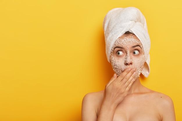 Zdziwiona młoda dziewczyna usuwa martwe komórki i bakterie z twarzy peelingiem z naturalną maską z soli morskiej, zakrywa usta dłonią, patrzy na bok, poddaje się zabiegowi na twarz