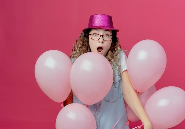 Zdziwiona młoda dziewczyna w okularach i różowym kapeluszu stojącym wśród balonów na białym tle na różowej ścianie