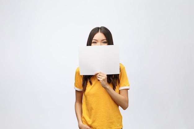 Zdziwiona młoda dziewczyna w żółtej koszuli z białą tabliczką w rękach