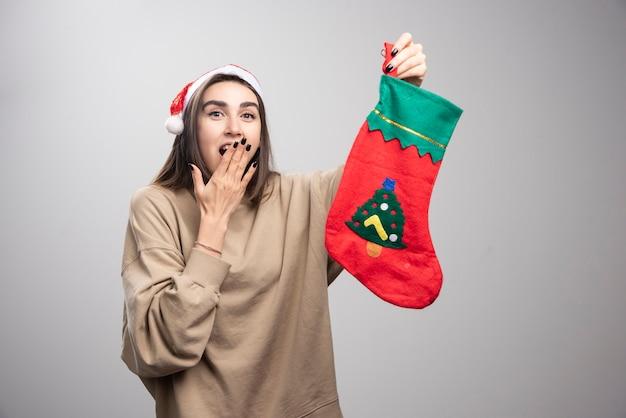 Zdziwiona młoda dziewczyna wyglądająca na zaskoczoną i trzymająca świąteczną skarpetę.