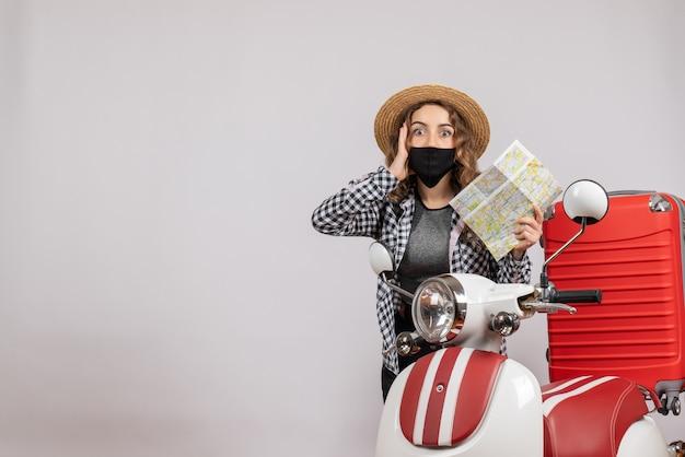 Zdziwiona młoda dziewczyna z maską trzymająca mapę stojąca w pobliżu motoroweru