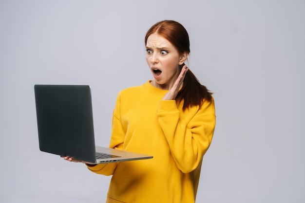 Zdziwiona młoda kobieta biznesu lub studentka z otwartymi ustami trzymająca otwarty laptop