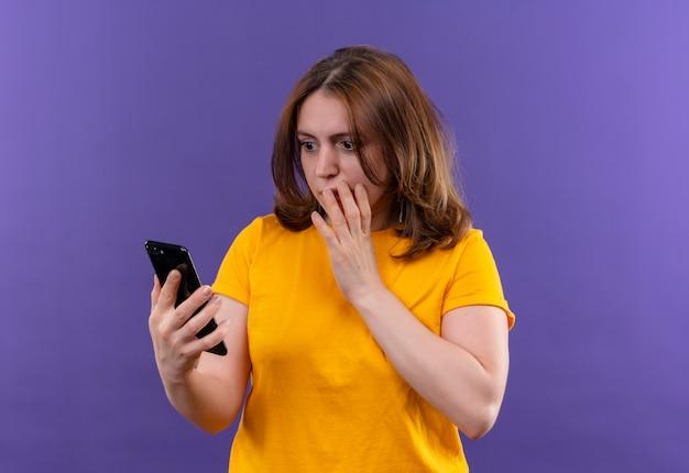 Zdziwiona młoda kobieta dorywczo trzymając telefon komórkowy i patrząc na niego ręką na ustach na odosobnionej fioletowej ścianie z miejsca na kopię