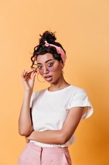 Zdziwiona młoda kobieta dotyka okularów przeciwsłonecznych