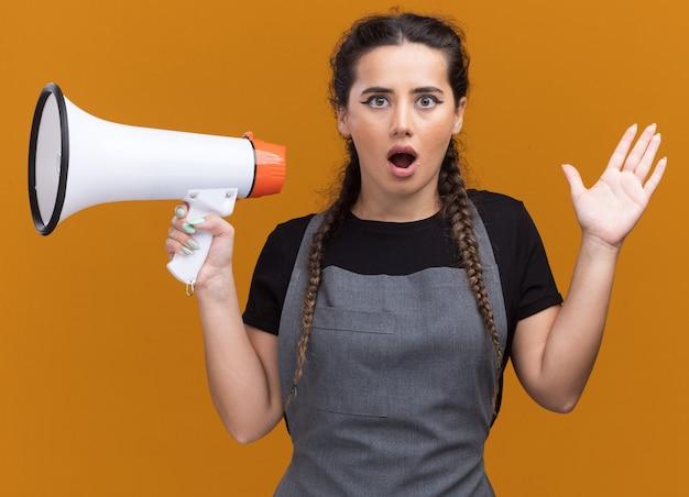 Zdziwiona młoda kobieta fryzjer w mundurze trzymając głośnik i rozkładającą rękę na białym tle na pomarańczowej ścianie